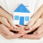 Руки взрослого и ребенка держат дом