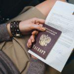 Женщина держит паспорт и бумаги