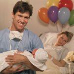 Отец держит новорожденного в роддоме
