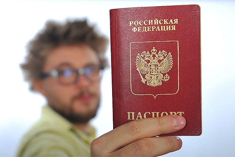 Держит в руке паспорт